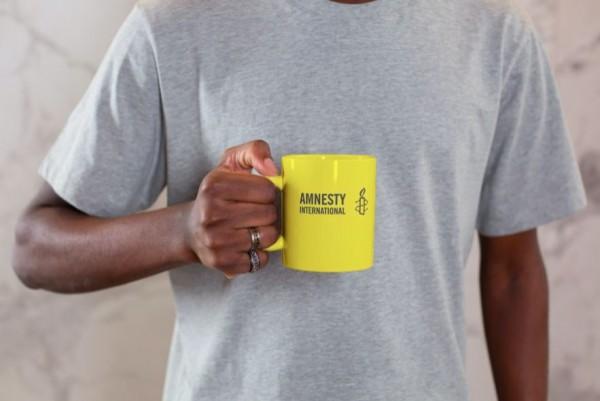 Gelbe Tasse mit schwarzen Amnesty International Logo